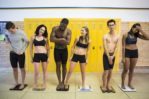 Group Of Young People Standing On Smart Scales