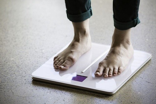 Man Standing On Smart Scale